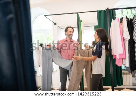 Assisting consultant. Kind polite well-mannered alluring dark-haired beaming bewitching consultant assistant the customer with choosing a new pair of pants