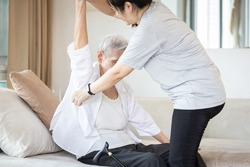 Assisting in dressing,asian female caregiver taking care of helping elderly patient get dress,chang clothes for senior mother,depressed old woman sit on the couch at home,preparing go to the hospital