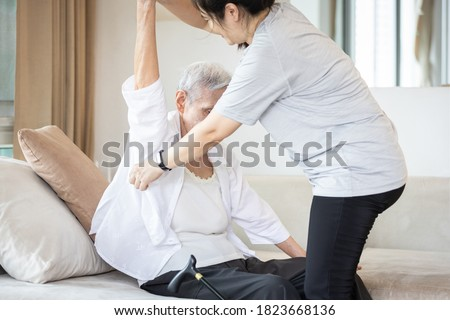 Assisting in dressing,asian female caregiver taking care of helping elderly patient get dress,chang clothes for senior mother,depressed old woman sit on the couch at home,preparing go to the hospital Stock photo ©