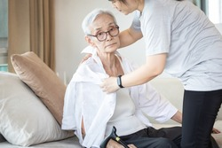 Assisting in dressing,asian female caregiver taking care of helping senior woman get dress,chang clothes for old mother,Alzheimer's elderly patient sit on the sofa at home,preparing go to the hospital
