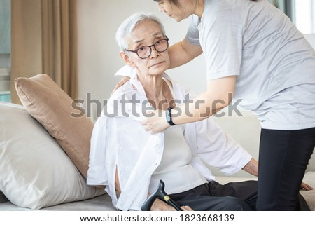 Assisting in dressing,asian female caregiver taking care of helping senior woman get dress,chang clothes for old mother,Alzheimer's elderly patient sit on the sofa at home,preparing go to the hospital Photo stock ©