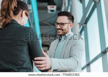 Associates handshaking after striking deal. Smiling businessman and businesswoman handshake. #796803382
