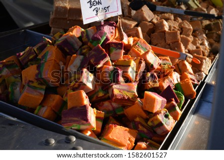 Assorted artisan fudge and other sweets for sale on a stall in an open air market