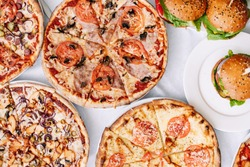 Assorted assorted pizzas and burgers on the table for tasting or working out the menu, top view