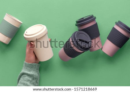 Assorted bamboo travel reusable coffee or tea cups or mags with silicone insulation.One cup with copy-space in female hand. Eco friendly zero waste solution for low impact sustainable lifestyle.