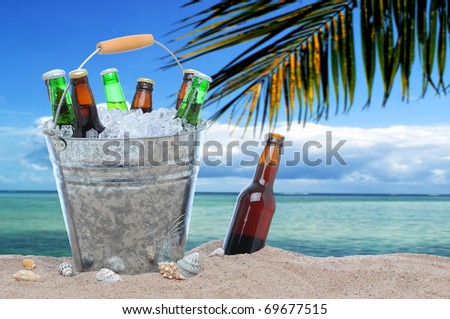 Assorted beer bottles in a bucket of ice in the sand on a tropical beach. One beer bottle without a cap is by itself stuck in the sand next to the pail.