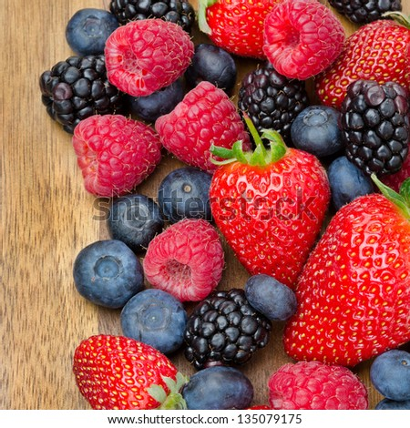 assorted berries on wooden background (strawberries, raspberries, blackberries, blueberries) closeup top view