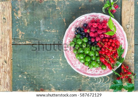 Assorted berries- raspberries, black and redcurrant, gooseberries from above, space for text