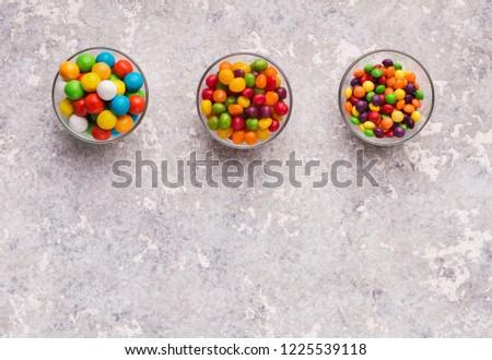 Assorted bon bon candies in bowls on concrete background, copy space