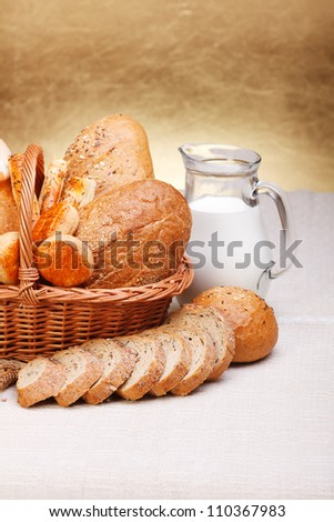 Assorted bread products with milk in jug on canvas