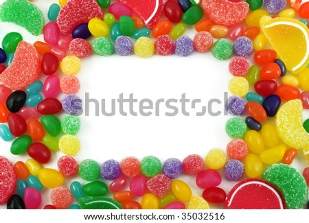 Assorted bright colored candy background with white copy space in center, horizontal