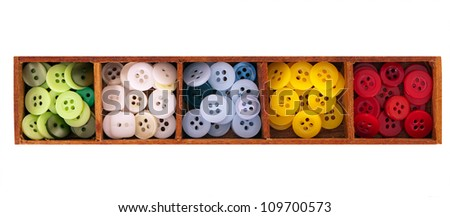 Assorted buttons in wooden box, isolated over white background