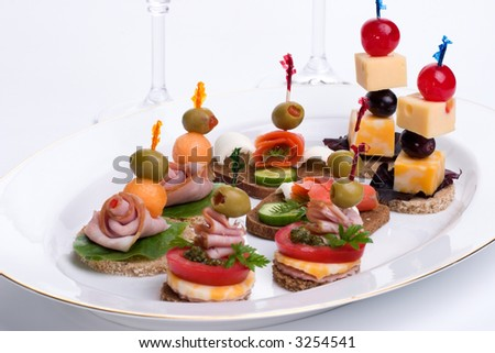 Assorted canapes sandwiches on plate over white background for Canape wines