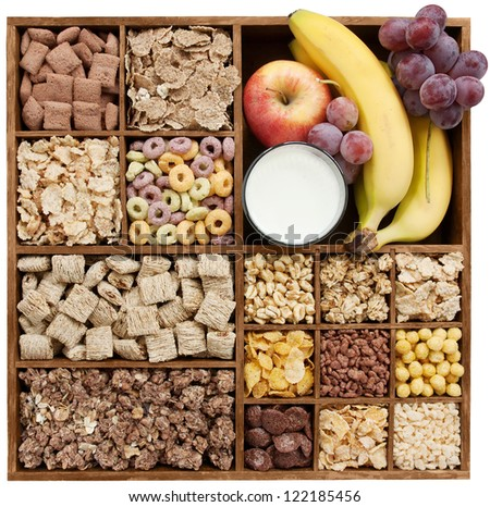 assorted cereals in wooden box with milk and fruits (manual focus)