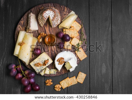 Assorted cheeses on round wooden board plate Camembert cheese, cheese grated bark of oak, hard cheese slices, walnuts, grapes, crackers, bread, thyme, dark black wood background, top view