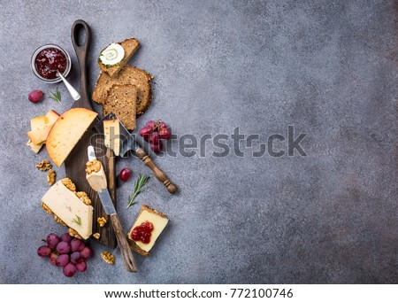 Assorted cheeses on wooden board plate, walnuts, grapes, bread on gray stone background, top view, flat lay, copy space.