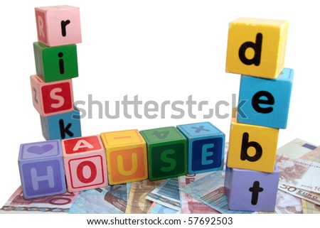 assorted childrens toy letter building blocks against a white background on money that spell house debt risk
