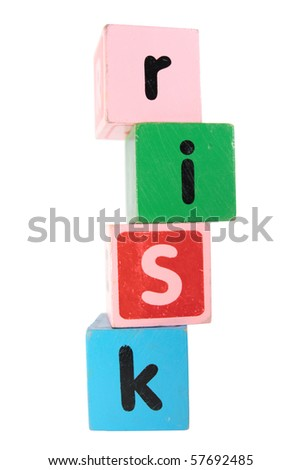 assorted childrens toy letter building blocks against a white background that spell risk