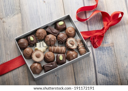 assorted chocolates confectionery in their gift box with red bow