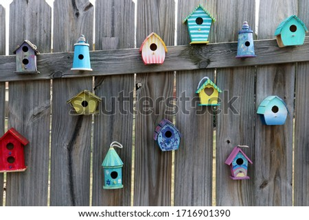 Assorted colored birdhouses hung on wooden fence ストックフォト ©