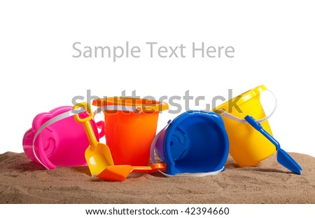 Assorted colored buckets including pink, orange, blue and yellow and shovels on a beach with copy space