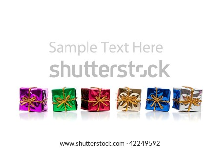 Assorted colored miniature Christmas presents including purple, red, gold, green and blue on  a white background with copy space