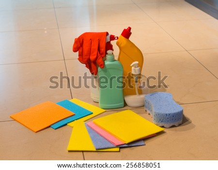Assorted colorful cleaning products displayed on a tiled floor including absorbent cloths, rubber gloves, sponge and plastic containers for disinfectants