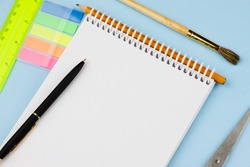 Assorted colorful office supplies on a light blue background. View from above. Education concept.