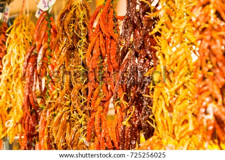 Assorted colorful varieties of hot and sweet dry peppers in the market. Rows of variety chili peppers hang together in bunches at market stall. Different forms, different colors. God for background #725256025