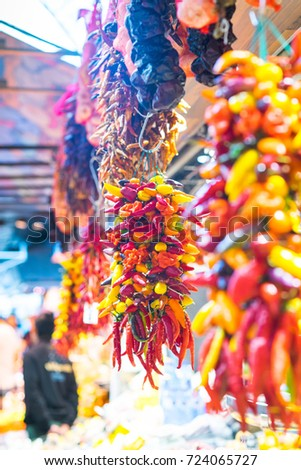 Assorted colorful varieties of hot and sweet peppers in the market. Rows of variety chili peppers hang together in bunches at market stall. Different forms, different colors.  #724065727