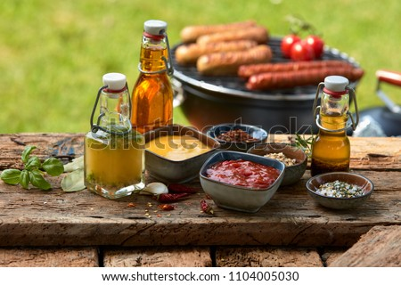 Assorted condiments and spices for a summer barbecue on a rustic wood picnic table outdoors in the garden with sausages grilling over a fire behind