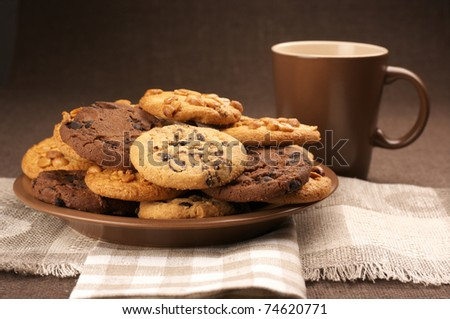 Assorted cookies in brown plate and brown mug of coffee on linen napkins.