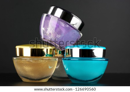 Assorted cosmetic creams on dark background.