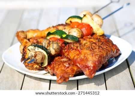 Assorted delicious grilled meat from chicken and pork and various vegetables on white plate on picnic table for family bbq party dinner
