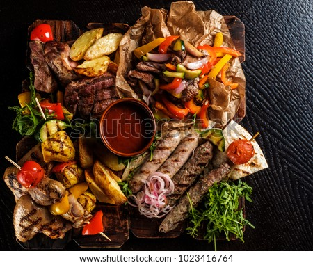 Assorted delicious grilled meat with vegetable. Mixed grilled bbq meat with vegetables. Mixed grilled meat on wooden platter. Top view.