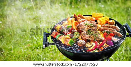 Assorted delicious grilled meat with vegetables on barbecue grill with smoke and flames in green grass