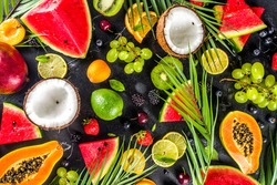 Assorted different summer tropical fresh raw fruits and berries. Clean eating, healthy lifestyle, diet and vitamin concept. Top view flatlay black table background