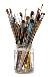 Assorted dirty painting brushes in glass flask