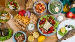 Assorted dishes of Greek Cuisine on table. souvlaki with chicken and french fries, Greek salad with feta, giros with chicken, Greek soup and dolma, top view on wooden table