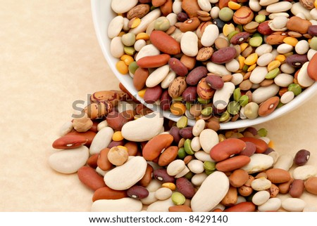 Assorted dry beans spilling from a dish resting on textured paper.