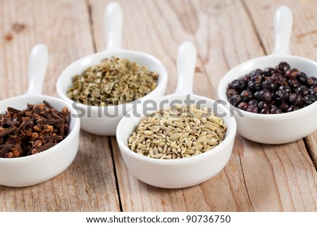 Assorted dry herbs and spices in white bowls over a wooden table