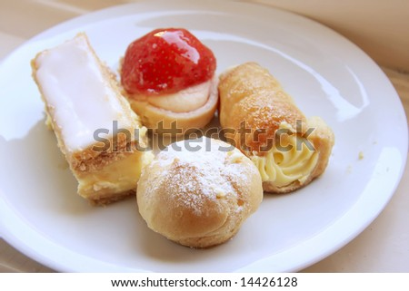 Assorted fancy cream pastry desserts on white plate