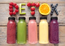 Assorted flavoured smoothie juices in bottles with detox spelt using fruits and vegetables