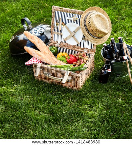 Assorted food sitting inside wicker picnic basket next to barbecue and bucket filled with bottles of beer
