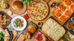 assorted foodset on table. Pizza Quattro formaggi on the Rome dough, pizza with parma ham, burges, shrimps, steak ribeye, french fries top view food.