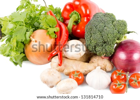 Assorted fresh organic vegetables, spices and herbs with garlic, onions, broccoli, tomatoes, bell pepper, mushrooms, chilli pepper, ginger and flat leaf parsley on a white background