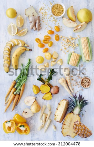 Assorted fresh raw organic produce in yellow hues, pepper capsicum carrot pineapple corn banana parsnip pear soya beans lentils quince, part of a color spectrum collection see more in my portfolio