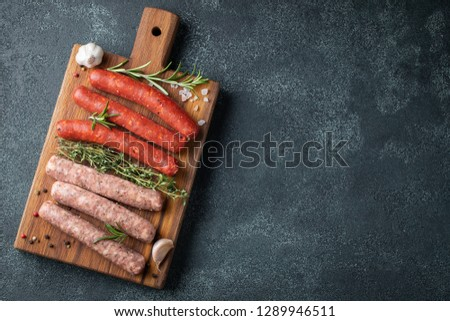 Assorted fresh sausages with thyme, rosemary, olive oil and garlic on a wooden chopping Board on a dark concrete table. Ready to cook sausages for dinner on black background. Top view with copy space Foto d'archivio ©