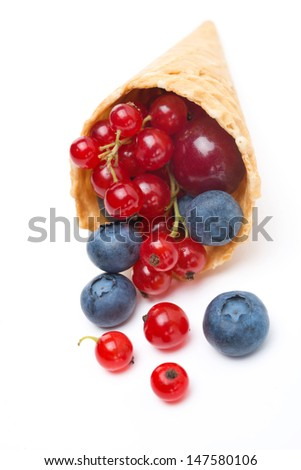 Assorted fresh seasonal berries in a waffle cone isolated on white background