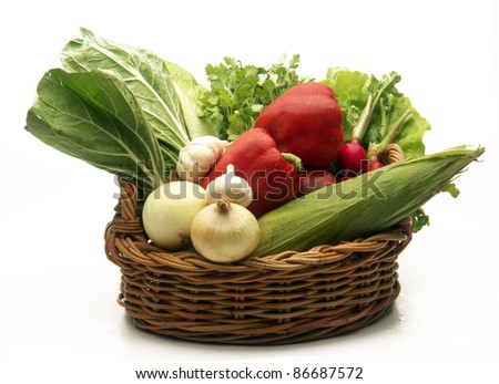 Assorted fresh vegetable basket on white background.